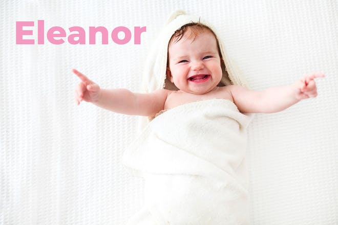 Baby wrapped in towel with arms spread wide. Name Eleanor written in text