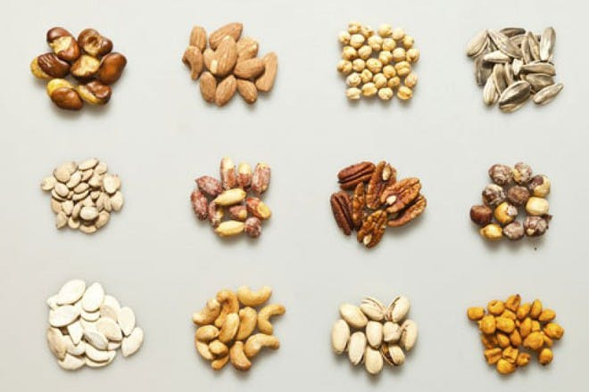 small piles of different nuts on grey background