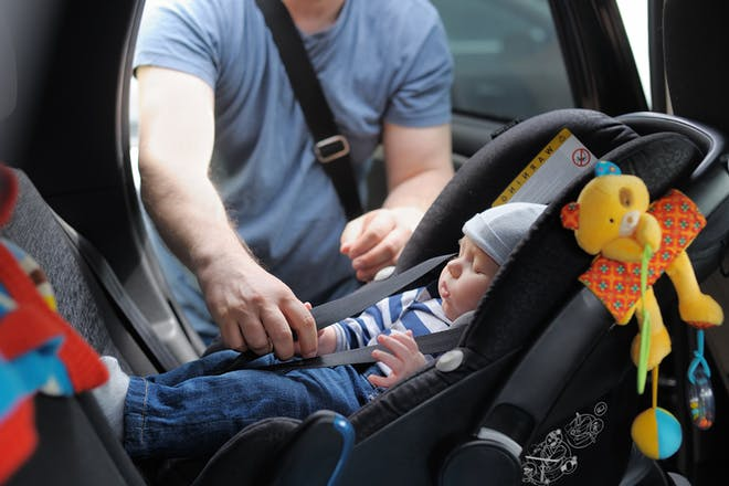 baby being strapped into car seat by dad