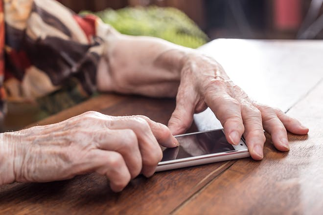 Old woman's hands holding a smartphone