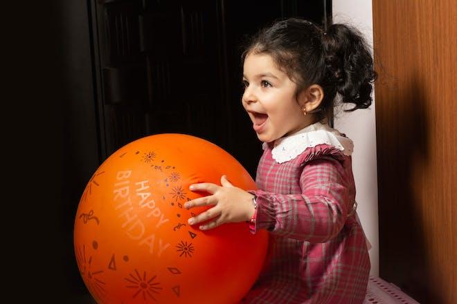 Girl holding balloon indoors
