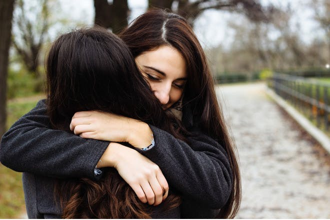 two women hugging in a park