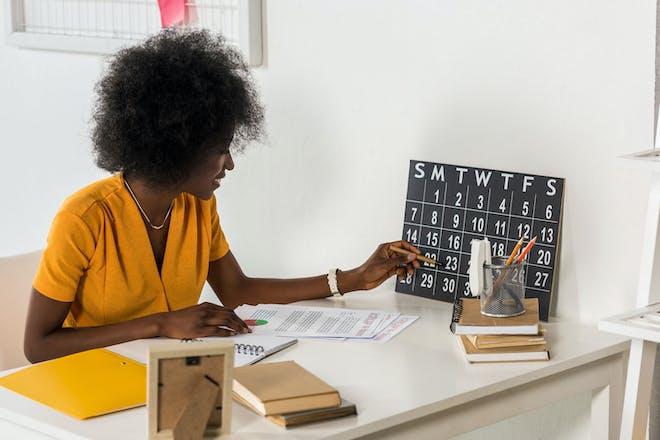 Woman sitting at desk looking at calendar