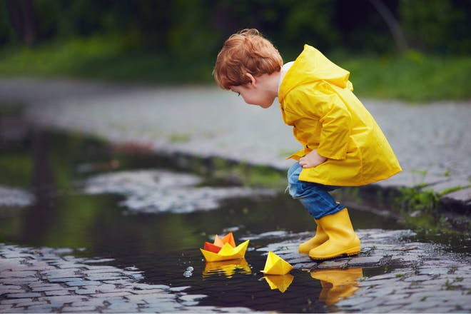 Child with paper boats in the river