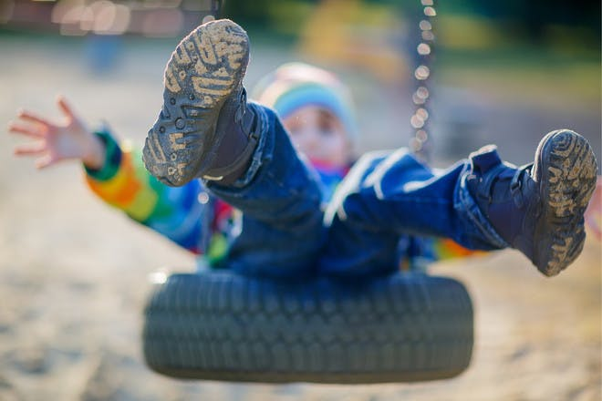 Child in wellies on a tyre swing