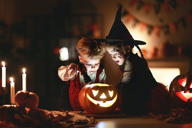 Boy and girl dressed as witches looking in pumpkin