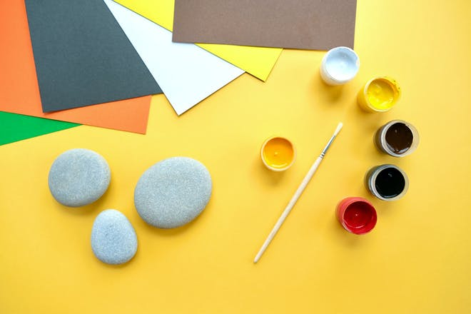 Pebbles on a yellow sheet of paper with paint and a paintbrush