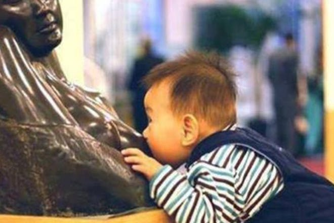 baby latching onto statue