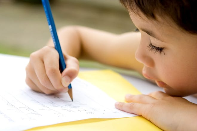 Young child writing a list