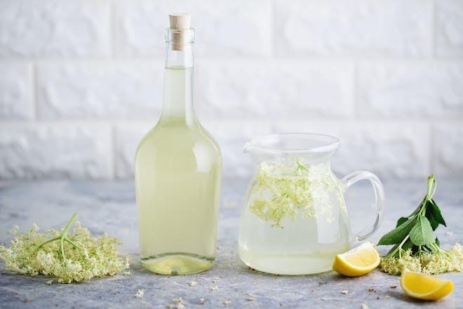 A bottle and jug of elderflower cordial with fresh elderflowers.