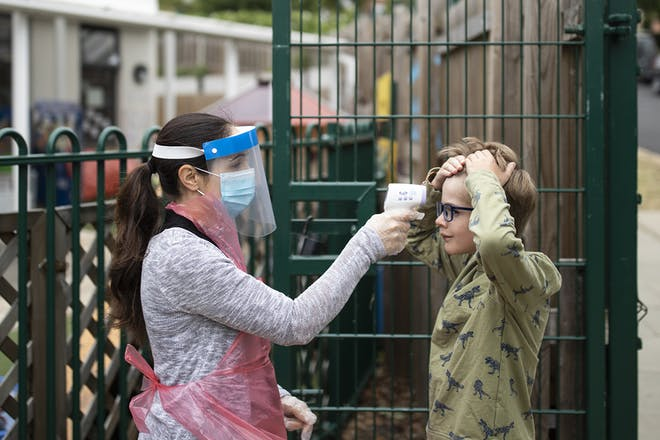 Child having their temperature tested at school