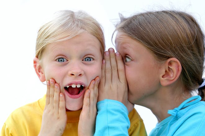 two girls whispering to each other