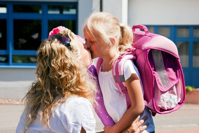 Mum kissing girl in reception in playground