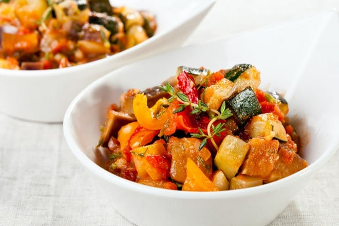 Vegetable goulash with courgettes, tomatoes and peppers in a white bowl
