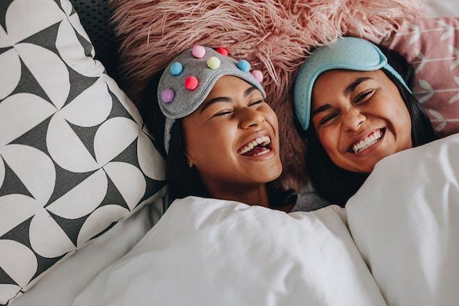 two teenage girls wearing eye masks laughing in bed