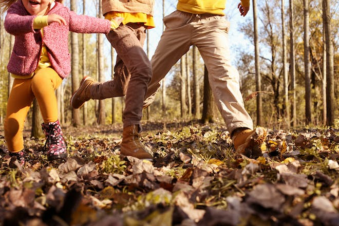 A toddler and two kids play three legged race through autumn leaves for Halloween