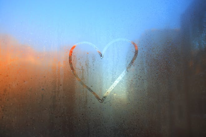 Love heart in the rain on window