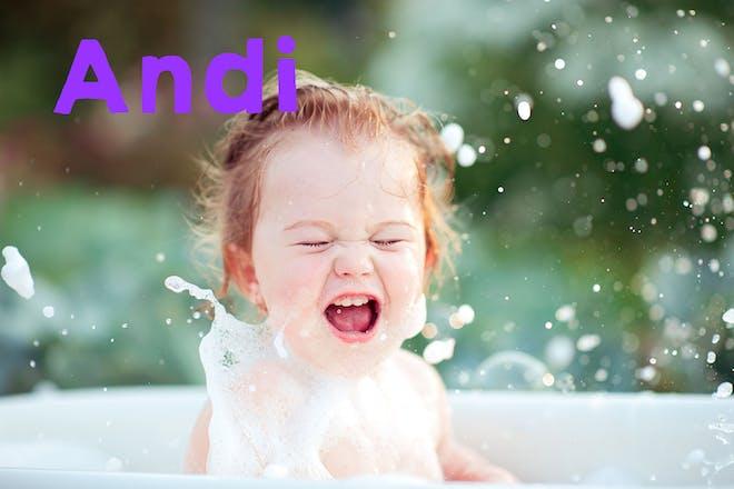 Toddler girl splashing in bath outdoors