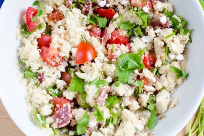 Bowl of couscous, tomato and feta salas with parsley