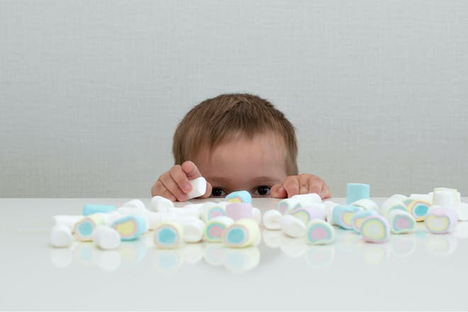Toddler placing lots of marshmallows on the table