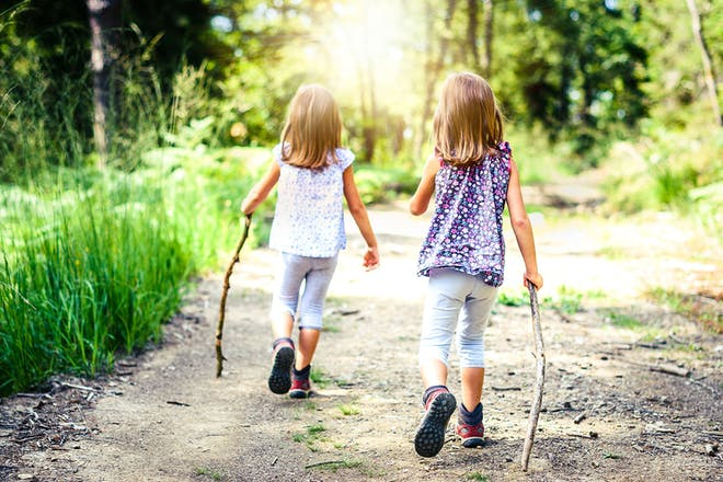 Two girls hiking in sunny forest
