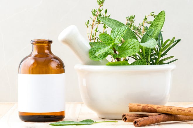 Brown medicine bottle, herbs in a pestle and mortar