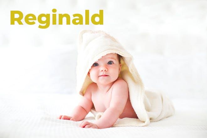 Baby wearing hooded towel. Name Reginald written in text