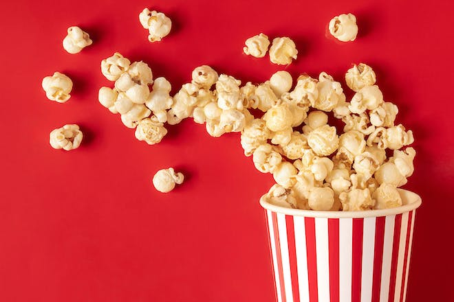 popcorn in a red and white striped bucket spreading onto red background