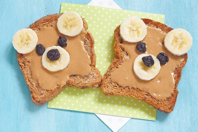 peanut butter on toast with banana slices for ears and raisins for eyes making it look like a bear