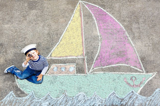 Child sitting on chalk drawing of boat