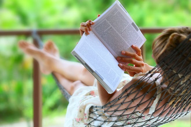 woman in hammock with book