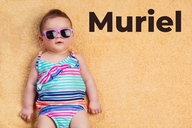 Baby on the beach with the words Muriel in text