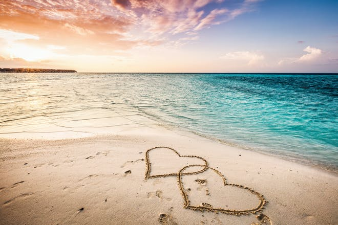 Beach and sea with hearts in the sand