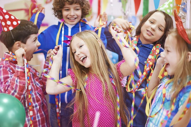 Children dancing at a party with streamers and hats