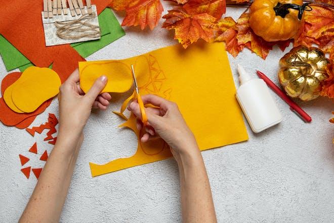 Cutting out orange paper to make DIY Halloween lanterns