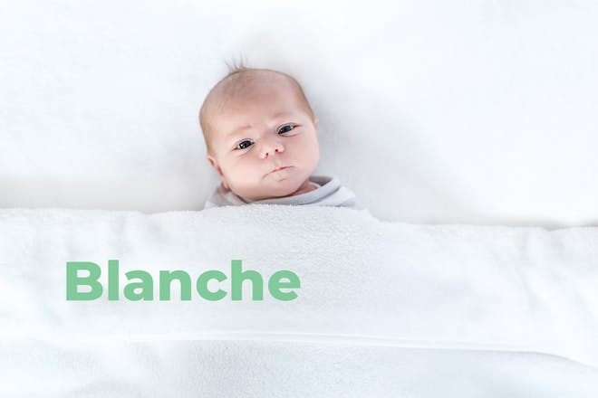 Baby looking quizzical lying under sheet. Name Blanche written in text