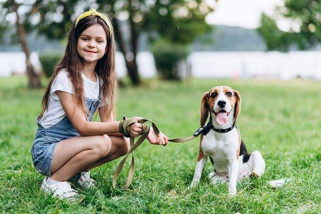 girl crouching down next to dog