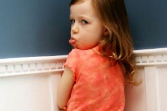 girl standing in corner pulling tongue