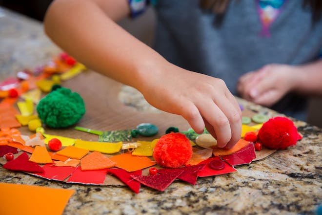 Child making collage of a rainbow