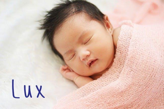baby sleeping under pink blanket