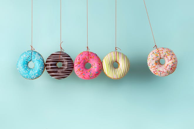 Five colourful doughnuts hanging on string