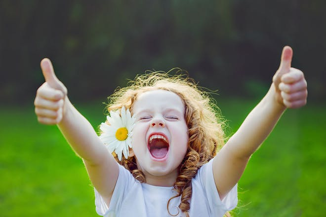 Young girl with daisy in hair giving thumbs up