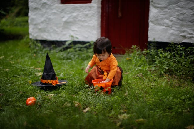 A toddler in an orange Halloween dress plays in the garden with a witch's hat and an orange bucket