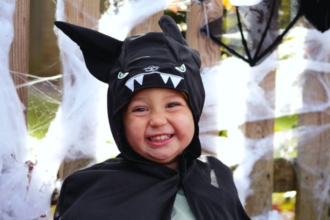 A toddler dressed in a bat onesie costume for Halloween