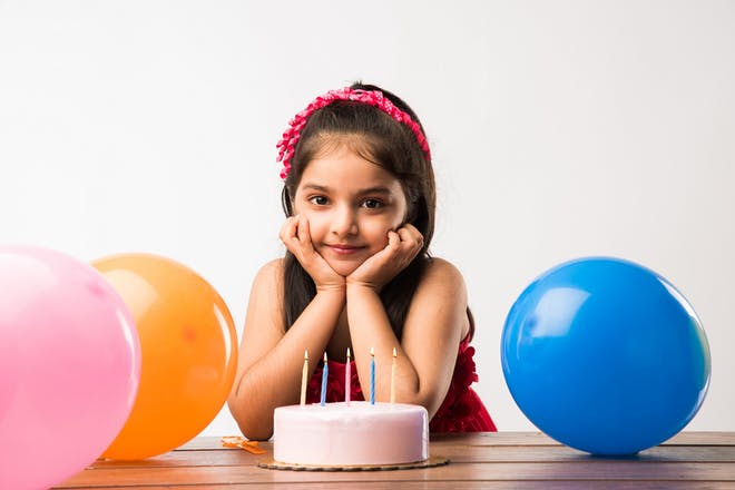 Girl in front of 5-year-old birthday cake