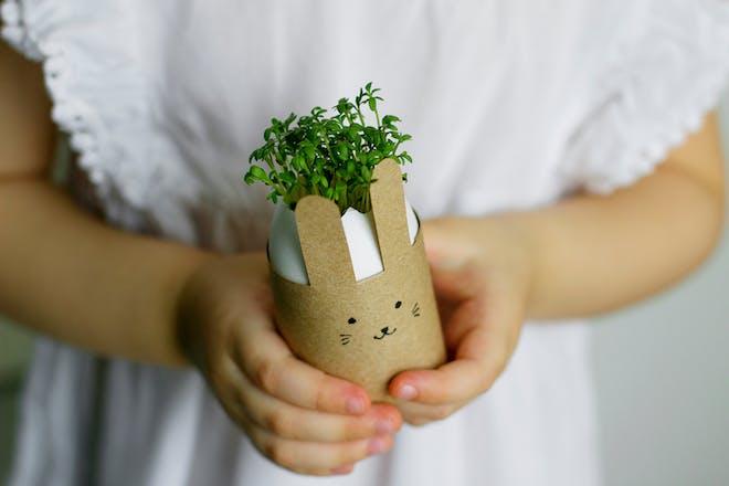 Child holding cress in cardboard rabbit pot