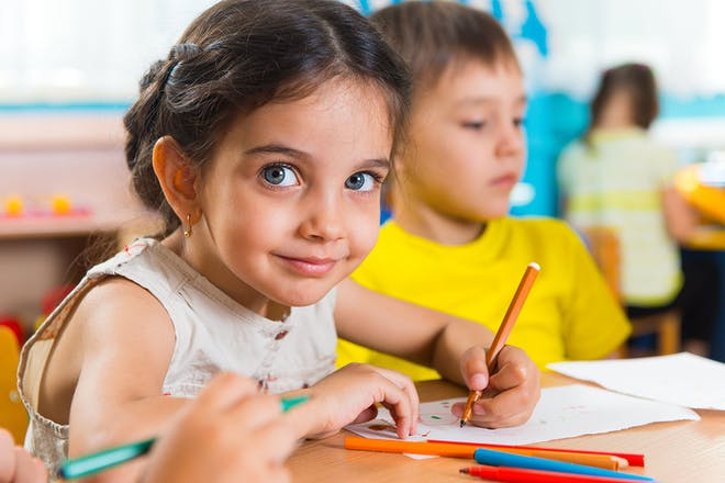 group of young children drawing in classroom