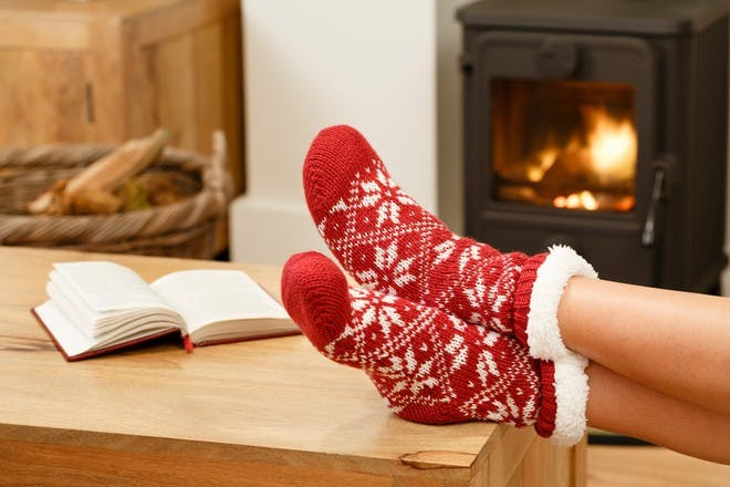 Woman's feet in red christmas socks sitting next to fire