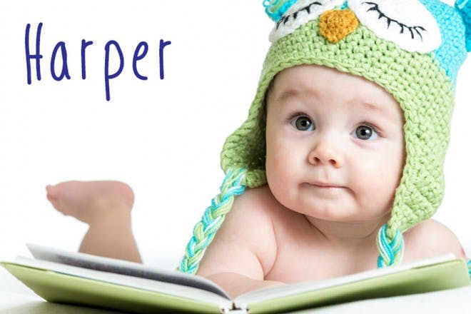 baby in woolly owl hat with book