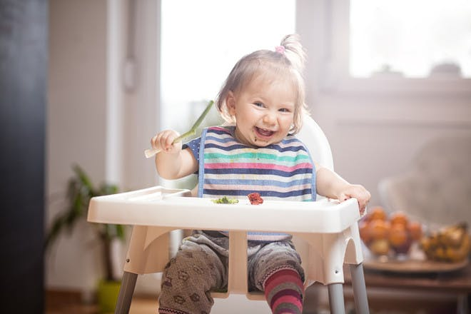 smiling baby girl in high chair
